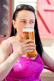 Woman drinking in a beer garden portrait Stock Images