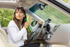 Woman drinking behind the wheel of her car Royalty Free Stock Photography