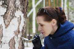 Woman drinking birch sap Stock Photography