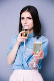 Woman drinking champagne and giving glass at camera Stock Photo