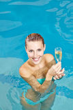 Woman drinking champagne. Happy young woman drinking champagne in swimming pool of hotel Stock Photo