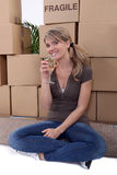 Woman drinking champagne near packing boxes. Woman drinking champagne surrounded by packing boxe Royalty Free Stock Image