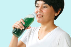 Woman drinking chlorophyll water. Woman drinking a bottle of chlorophyll water Stock Images