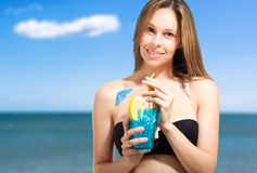 Woman drinking a cocktail on the beach Stock Photos