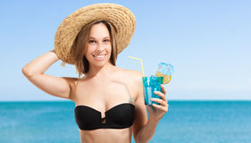 Woman drinking a cocktail on the beach Stock Images
