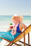 Woman drinking a cocktail in her deck chair Royalty Free Stock Photo