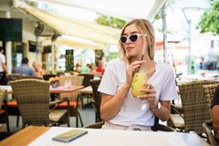 Young Woman drinking cocktail lemonade in cafe royalty free stock images