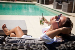 Woman drinking cocktail at poolside. Beautiful woman in white summer dress laying with mojito cocktail on lounge chair at poolside. Luxury vacation Royalty Free Stock Photography