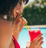 Woman drinking cocktail at the poolside Stock Photography