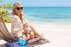 Woman drinking cocktail and relaxing in chair on the beach Stock Photography