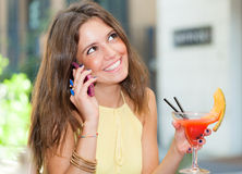 Woman drinking a cocktail and talking on the phone Royalty Free Stock Photos