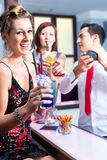 Woman drinking cocktails in cocktail bar. Woman drinking cocktails in fancy night club Royalty Free Stock Photo