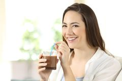 Woman drinking cocoa shake looking at camera. Happy woman drinking cocoa shake looking at camera sitting on a couch in the living room at home Stock Image