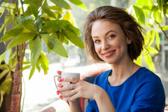 Woman drinking coffe in a coffee shop. Beautiful young woman. Coffe lovers Stock Images