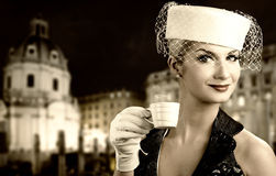 Woman drinking coffee. Beautiful young woman drinking coffee. Old city background behind her Stock Image