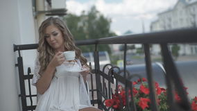 Woman drinking coffee on the balcony stock video footage