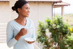 Woman drinking coffee balcony. Pretty african american woman drinking coffee on balcony Royalty Free Stock Photography
