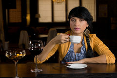 Woman drinking coffee at a bar counter. Attractive stylish woman sitting alone drinking coffee at a bar counter with a large glass of red wine in the foreground stock image
