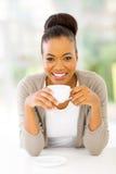 Woman drinking coffee. Beautiful african american woman drinking coffee at home Stock Images