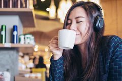 Woman drinking coffee. A beautiful Asian woman close her eyes and listening to music with headphone while drinking coffee with feeling happy and relax in modern Stock Image