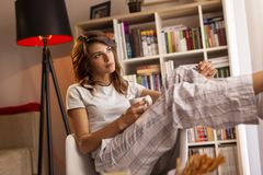 Woman drinking coffee. Beautiful young woman wearing pajamas, sitting next to the living room window, holding a cup of coffee and enjoying the moment stock image