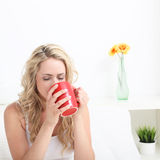 Woman drinking coffee in bed Royalty Free Stock Photography