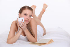 Woman drinking coffee in bed Royalty Free Stock Images
