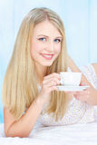 Woman drinking coffee in bed Royalty Free Stock Photo