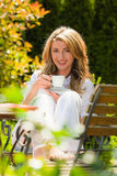Woman drinking coffee at breakfast in the garden Royalty Free Stock Image