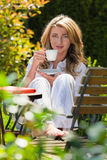 Woman drinking coffee breakfast in the garden. Young woman drinking a cup of coffee for breakfast in the garden Stock Photography