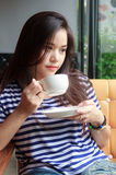 Woman drinking coffee at cafe Stock Images