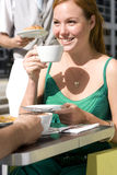 Woman drinking coffee in cafe, outdoors, smiling Stock Photo