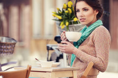 Woman drinking coffee in a cafe on the streets Royalty Free Stock Images