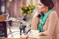 Woman drinking coffee in a cafe on the streets Royalty Free Stock Photography