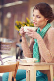 Woman drinking coffee in a cafe on the streets Royalty Free Stock Photos