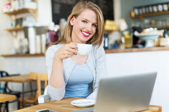 Woman drinking coffee at cafe Royalty Free Stock Photos