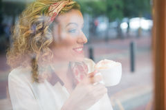 Woman drinking coffee in cafeteria seen through window Stock Photo