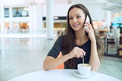 Woman drinking coffee and calling with cellphone royalty free stock image