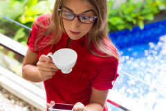 Woman drinking coffee checking Mails on phone Stock Photography