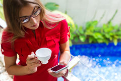 Woman drinking coffee checking Mails on phone Royalty Free Stock Image