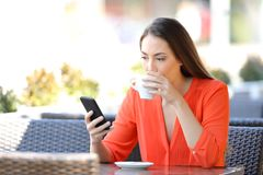 Woman drinking coffee checking smart phone in a bar. Serious woman drinking coffee checking smart phone content sitting in a bar terrace stock image