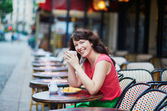 Woman drinking coffee with croissant in Parisian cafe. Beautiful young woman drinking coffee and eating croissant in traditional Parisian outdoor cafe, Paris Stock Images