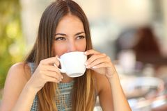 Woman drinking a coffee from a cup in a restaurant terrace. While thinking and looking sideways stock photography