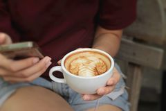 Woman drinking coffee in cup and smart phones Stock Photos