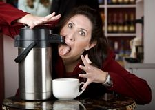 Woman drinking coffee directly from a dispenser Stock Image