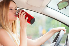 Woman drinking coffee while driving her car Stock Photography
