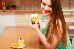 Woman drinking coffee and eating delicious cake. Royalty Free Stock Image