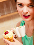 Woman drinking coffee and eating delicious cake. Royalty Free Stock Images