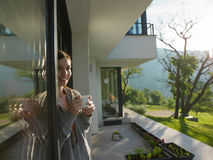 Woman drinking coffee in front of her luxury home villa Stock Photo