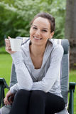 Woman drinking coffee in garden Stock Images